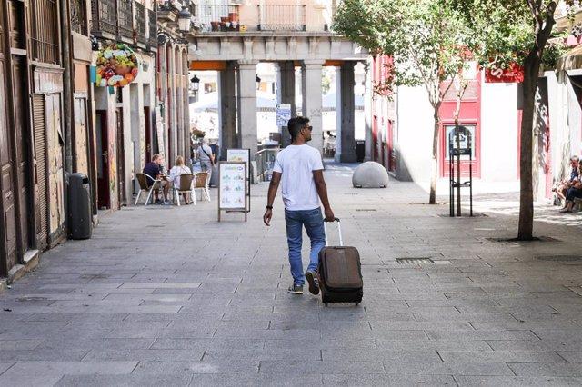 Imagen de recurso de un turista que pasea con una maleta por el centro de Madrid.
