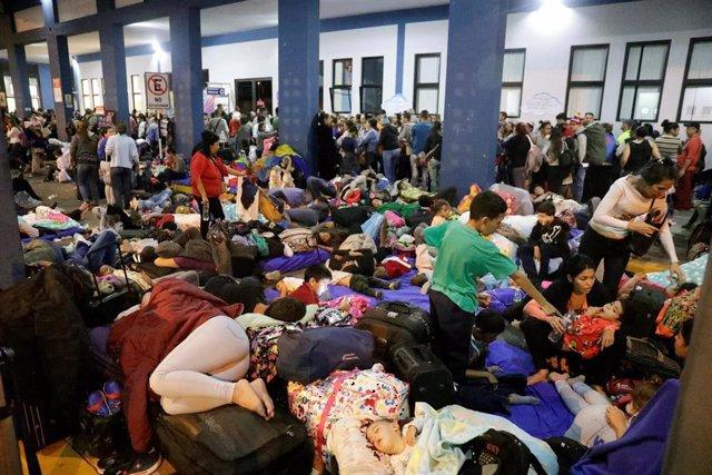 Migrantes venezolanos esperan en un puesto fronterizo en Perú