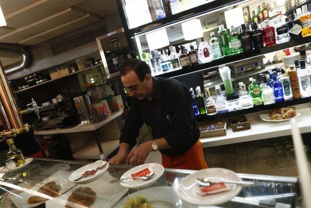 Un camarero sirve unos platos.