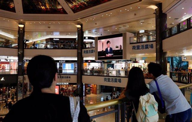 Hongkoneses siguen en un centro comercial la intervención de la jefa de Gobierno, Carrie Lam