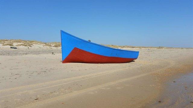 Una patera vacía en la playa.
