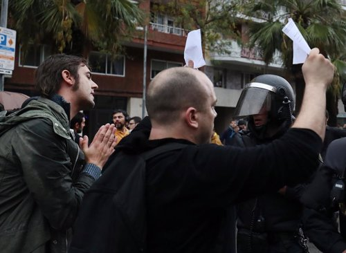 People hold up ballot sheets to riot police outside a polling station for the ba