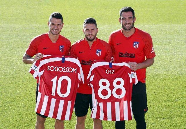 Los jugadores del Atlético Vitolo, Koke y Adán con la camiseta de Socios.Com