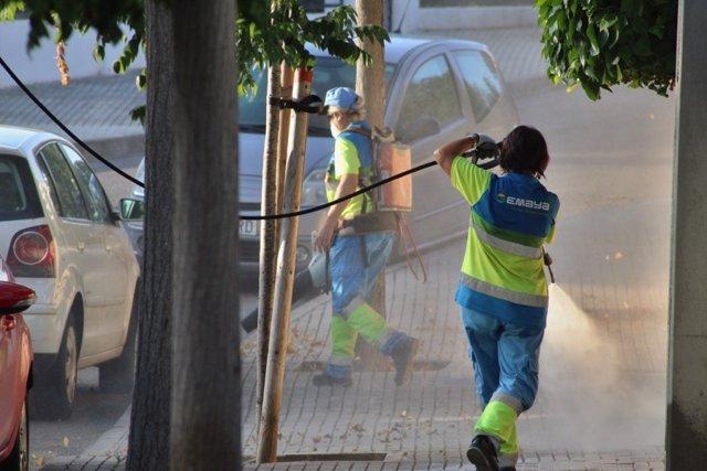 Operarios de Emaya limpian en una calle con mangueras.
