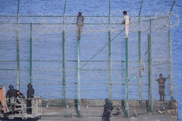En la imagen, tres de un total de 153 migrantes, entran en Ceuta saltando su doble valla en la primera incursión en grupo en un año.