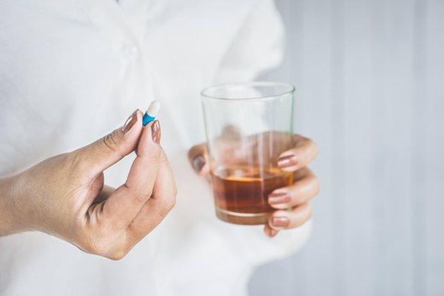 Mujer  tomando medicamentos con un vaso de alcohol