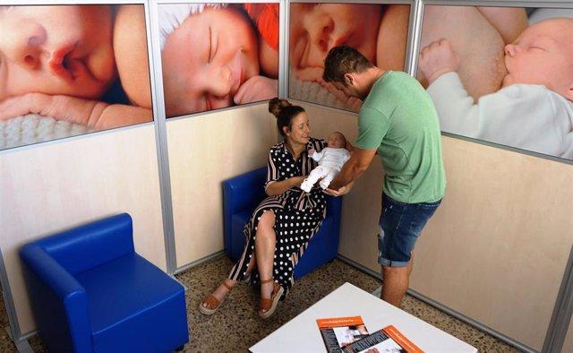 Una pareja, con su hijo recién nacido, en el punto de lactancia del Hospital de Tudela