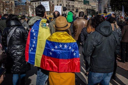 Participantes en la manifestación en Barcelona para respaldar el apoyo de la Unión Europea a Venezuela y el reconocimiento a Juan Guaidó como presidente interino visten banderas venezolanas.
