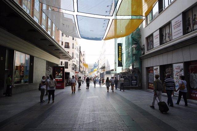 Turistas y vecinos de la zona Centro de Madrid pasean por la calle Preciados bajo la sombra gracias a los toldos instalados