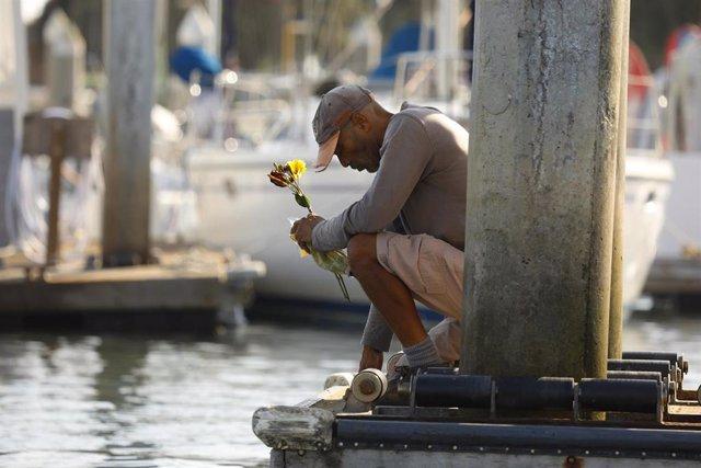 Un hombre pone flores en honor a las víctimas de la tragedia del Conception.