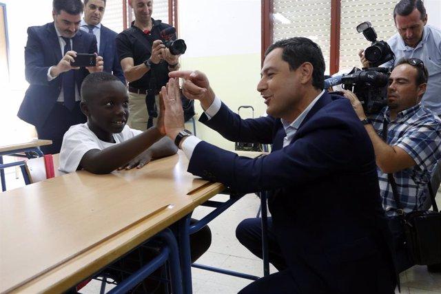 El presidente de la Junta de Andalucía, Juanma Moreno, con algunos alumnos  del colegio de Educación Infantil y Primaria 'Manuel Altolaguirre' de Málaga, en la apertura del curso escolar