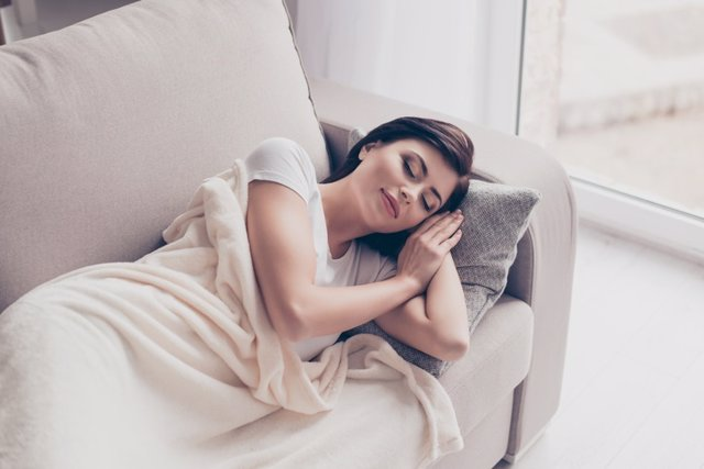 Una joven duerme se hecha la siesta en el sofá.