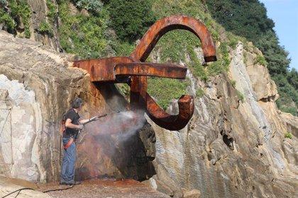 Expertos de Chillida Leku limpian los lazos amarillos pintados en el Peine del Viento