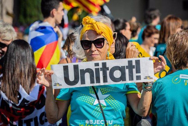Un dona subjecta un cartell en el qual es llegeix 'Unitat' (Unitat)  durant la manifestació convocada per l'Assemblea Nacional Catalana (ANC) amb el lema 'Objectiu Independència (Objectiu independència)', dins dels actes de la Diada de Catalunya 2019, en