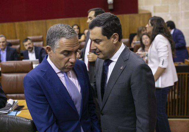 El presidente de la Junta de Andalucía, Juanma Moreno (d), conversando con el consejero de Presidencia, Elías Bendodo (i).