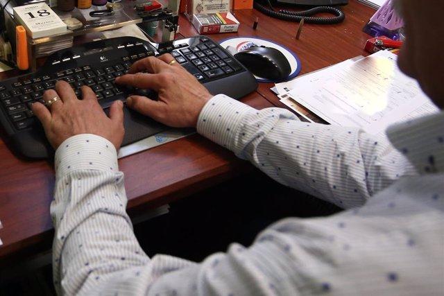 Un home treballant en una oficina.