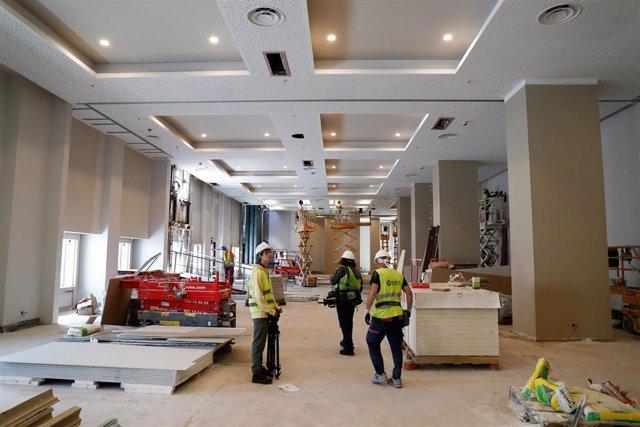 Operarios de obras durante el proceso final de la remodelación de uno de los salones del hotel Rui Plaza España, en el edificio España.