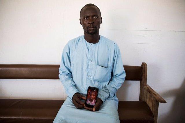 Un padre nigeriano muestra la foto de su hijo desaparecido