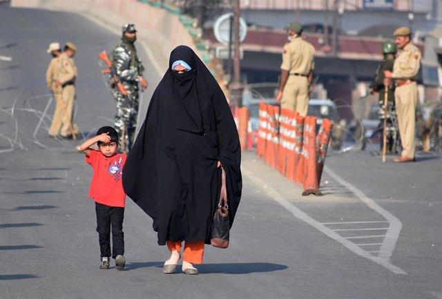 Una mujer con su hijo cerca de un puesto de control militar en la Cachemira india