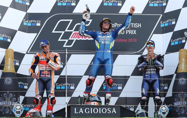 25 August 2019, England, Towcester: Second-placed Spanish motorcycle racer Marc Marquez of Repsol Honda (L-R), winner Spanish Alex Rins of Suzuki and third-placed Spanish Maverick Vinales of Movistar Yamaha celebrate on the podium after the end of the 201