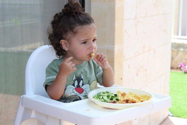 Niña pequeña comiendo.