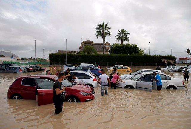 Afectats pel temporal amb els seus cotxes parcialment submergits a Oriola (Alacant).