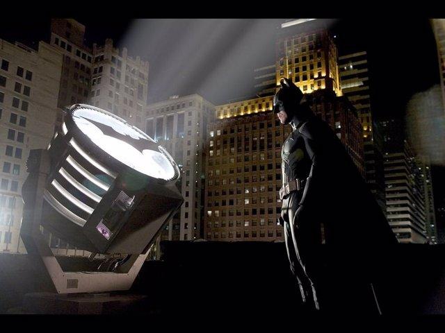 Batman frente a la Batseñal en los tejados de Gotham