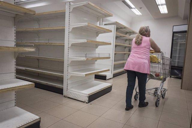 Una mujer en un supermercado prácticamente vacío en Caracas