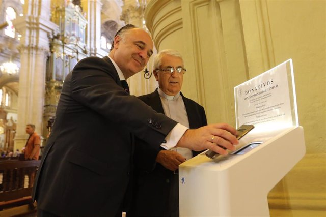 El director territorial de CaixaBank en Andalucía Oriental y Murcia, Juan Ignacio Zafra  acompaña all déan de la Catedral de Málaga, Antonio Aguilera, a conocer el funcionamiento de los nuevos cepillos digitales