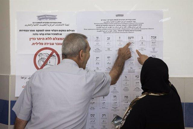 Dues persones es preparen per votar durant les eleccions d'Israel.