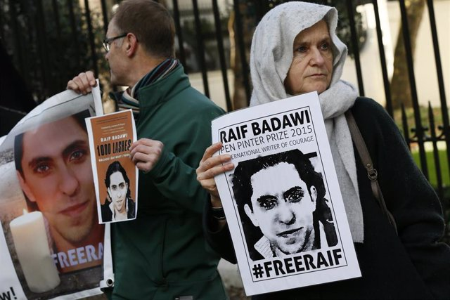 Manifestantes con carteles con la imagen del bloguero Raif Badaui frente a la Embajada de Arabia Saudí en Londres, Reino Unido