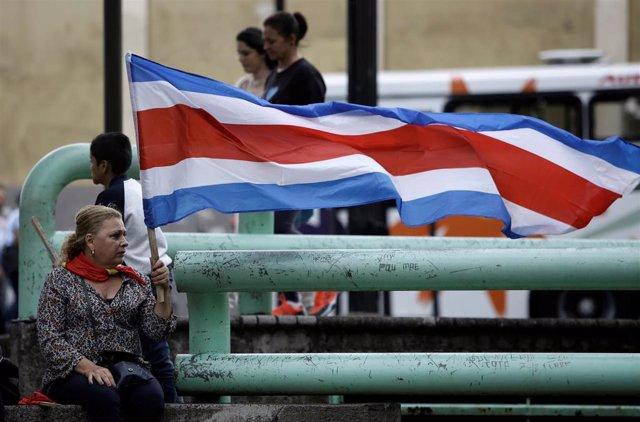 Una mujer con una bandera de Costa Rica