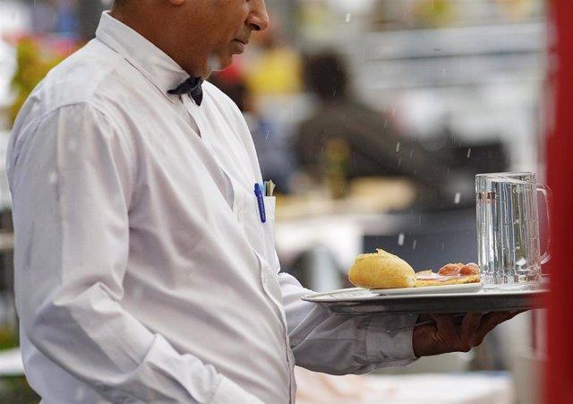Un camarero porta una bandeja en un bar de Madrid.