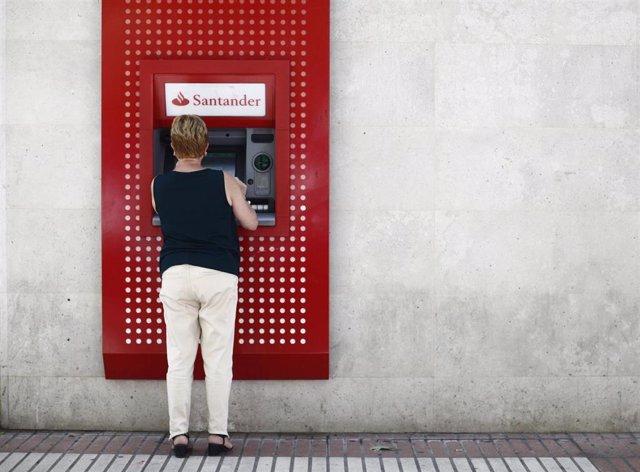 Imagen de recurso de una mujer saca dinero en un cajero del Banco Santander.