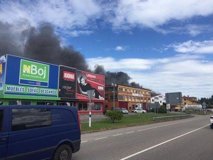 Los Bomberos trabajan para sofocar un incendio en una nave de carrocería en Siero