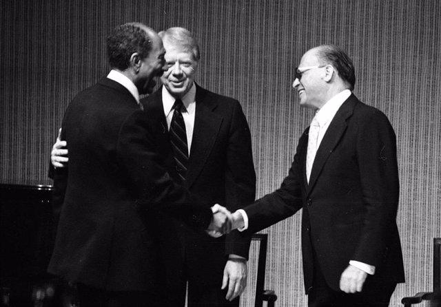 El presidente egipcio Anwar Sadat estrecha la mano del primer ministro israelí Menachem Begin ante la mirada del presidente estadounidense Jimmy Carter en 1978