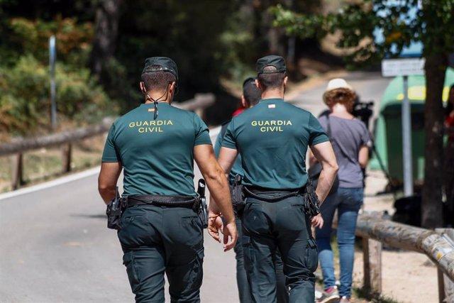Dos agentes de la Guardia Civil, en las inmediaciones del Hotel Cirilo de Cercedilla, que actúa de centro base del dispositivo de búsqueda de la exesquiadora Blanca Fernández Ochoa, desaparecida en la sierra de Madrid el pasado 23 de agosto.