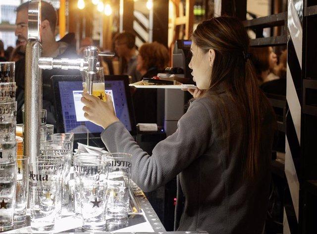 Una cambrera serveix una cervesa en un bar