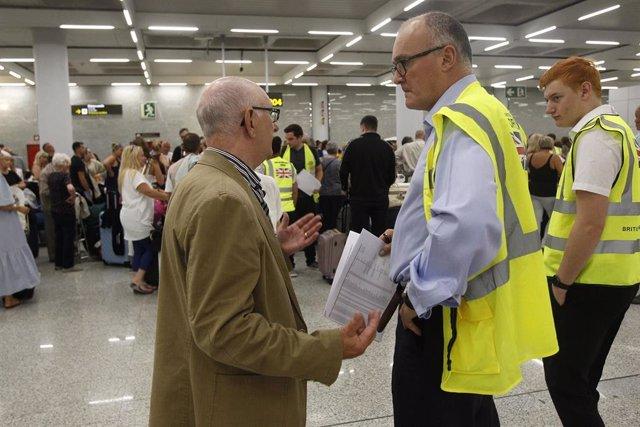 Un turista habla con dos guardas de seguridad mientras se forman largas colas en las ventanillas del aeropuerto de Palma de Mallorca (Baleares), horas después de que la compañía británica Thomas Cook anunciase su quiebra y de que varios de sus vuelos fu