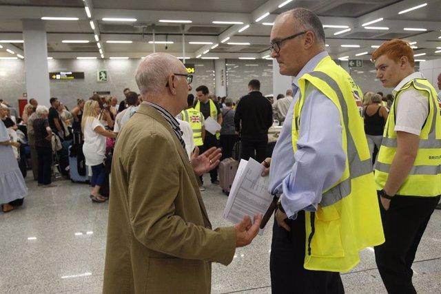 Un turista parla amb personal de seguretat a l'aeroport de Palma de Mallorca després de la fallida de Thomas Cook.