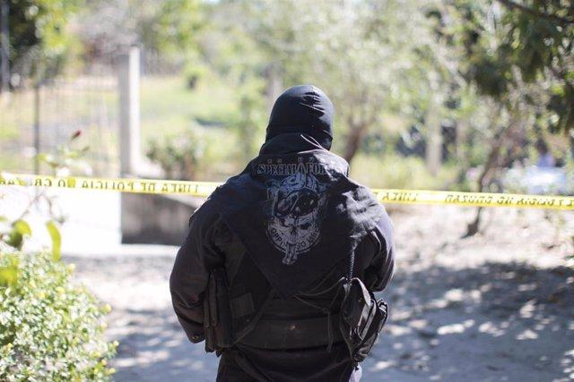 Un policía vigila la escena de un crimen en El Salvador