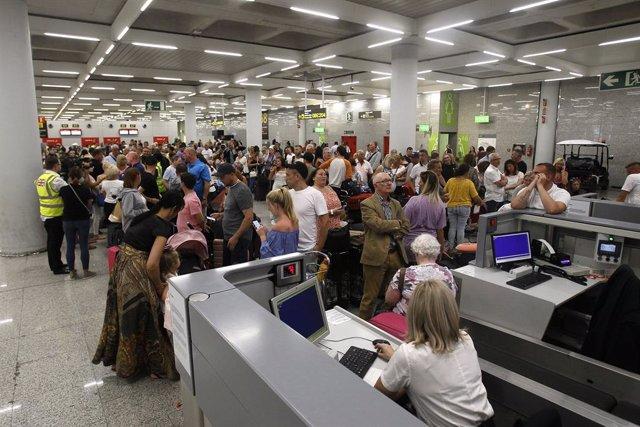 Diversos turistes fan cua enfront dels mostradors de la companyia Thomas Cook en l'aeroport de Palma de Mallorca (Balears), hores després que la companyia britnica anunciés la seva fallida, a 23 de setembre de 2019.