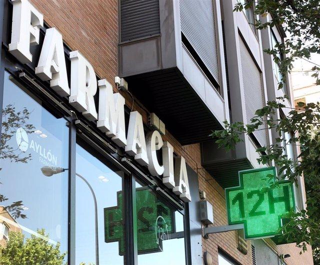 La entrada de una famacia con una señal luminosa de la cruz verde en la que pone 12h.