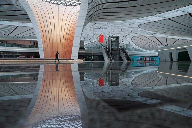 Un trabajador pasea por una terminal en el aeropuerto de Internacional de Daxing, en Pekín