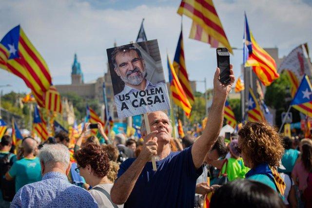 Un home subjecta un cartell amb la foto del president d'mnium Cultural, Jordi Cuixart, en el qual es llegeix `Us volem a casa juntament amb banderes estelades