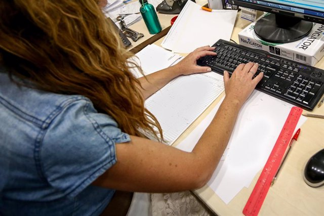 Una dona escriu en el teclat del seu ordinador, amb papers al voltant mentre treballa a l'oficina.