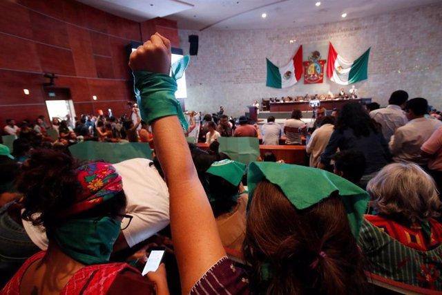 Una anifestante proaborto levanta el puño durante una sesión del congreso local mientras los legisladores votan sobre una legislación que despenalizaría el aborto en Oaxaca