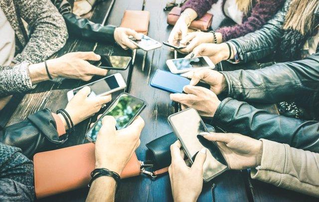Jóvenes compartiendo contenido en redes sociales con teléfonos inteligentes móviles