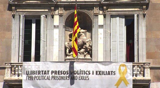El palau de la Generalitat torna a penjar una pancarta en la qual es llegeix 'Llibertat presos polítics i exciliats', juntament amb un lla groc, un dia després de les eleccions autonmiques, municipals i europees.