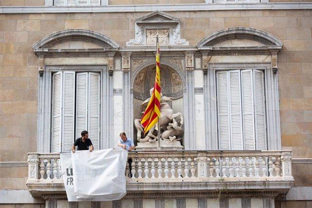 Retiren la pancarta con el lla groc de la faana de la Generalitat.
